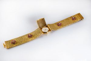 A Bucherer 18K gold, ruby and diamond bracelet with a hidden watch